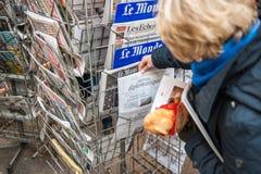 Fransyska som köper den politiska tidskriften royaltyfri fotografi