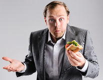 Frantic pace of life. Busy businessman eating takeaway sandwich on the go, shrugging to the fast pace of life Royalty Free Stock Photos