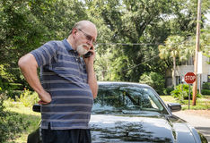 Frantic senior man on cell phone in road next to c. Angry elderly man on cell phone calls for roadside assistance for car malfunction or breakdown emergency. He Stock Images