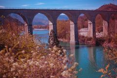 Französische Bogenbrücke auf einem Fluss mit blühenden Bäumen im Vordergrund lizenzfreie stockbilder