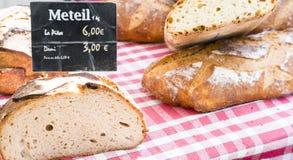 Französische Brote mit generischem Preis unterzeichnen auf Rot überprüftem Stoff im französischen Markt stockfotografie