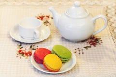 Französische bunte macarons auf einer Platte, einer Schale und einer Teekanne Stockfoto
