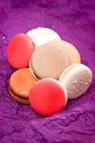 Französische bunte macarons auf violettem Hintergrund Stockfotos