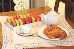 Französische bunte macarons in einem Kasten, in den Hörnchen, in der Schale und in der Teekanne Stockbild