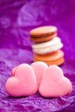 Französische bunte macarons mit Herzen auf violettem Hintergrund Stockbild