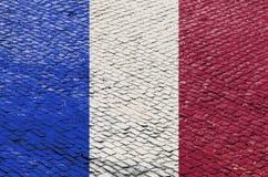Französische Flagge auf einem Kopfstein-Straßen-Muster stockfotos