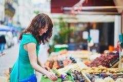 Französische Frau, die Früchte auf Markt wählt Lizenzfreie Stockbilder