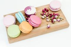 Französische köstliche bunte macarons Plätzchen und kleine Rosen auf hölzernem Schreibtisch Weißer Hintergrund Lizenzfreie Stockbilder