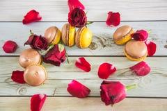 Französische macaruns mit roten Rosen Stockbilder