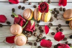 Französische macaruns mit roten Rosen und Kaffee Lizenzfreie Stockfotografie