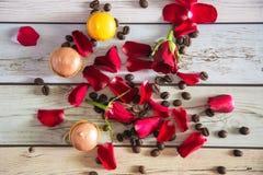 Französische macaruns mit roten Rosen und Kaffee Lizenzfreies Stockfoto