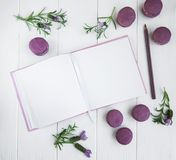 Französische Makronen, sauberes Notizbuch und Lavendelblumen Stockfotografie