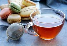 Französische Makronen und eine Tasse Tee lizenzfreies stockbild
