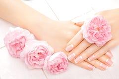 Französische Maniküre mit rosafarbenen Blumen Badekurort stockbild
