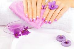 Französische Maniküre mit violetten Blumen Badekurort stockbilder