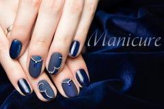 Französische Maniküre - schöne manikürte weibliche Hände mit blauer Maniküre mit Bergkristallen auf dunkelblauem Hintergrund lizenzfreie stockfotos