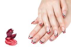 Französische Maniküre - schöne manikürte weibliche Hände mit roter Schwarzweiss-Maniküre mit den Bergkristallen lokalisiert auf w lizenzfreies stockbild