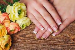 Französische Nagelkunst in der Goldfarbe Stockfotos