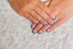 Französische Nagelkunst mit den hellblauen und Goldlinien stockfotografie