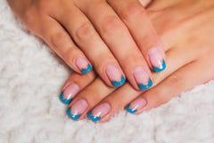 Französische Nagelkunst mit den hellblauen und Goldlinien stockbild