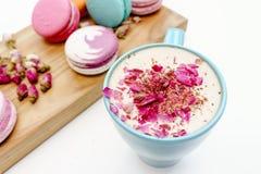 Französische schöne macarons auf hölzernem Schreibtisch und blauer Schale Aromacappuccino Lizenzfreies Stockbild
