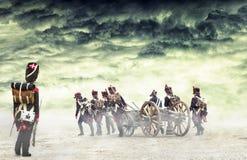 Französischer Grenadier, der napoleonische Soldaten zu marschieren aufpasst und eine Kanone im einfachen Land, Landschaft zu zieh Stockbilder