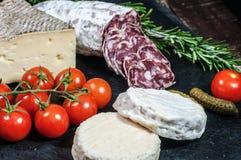 Französischer Käse, Salami, Tomaten und Essiggurken Stockfotos