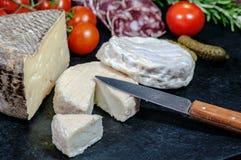 Französischer Käse, Salami, Tomaten und Essiggurken Stockfotografie