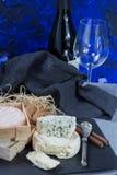 Französischer Rotwein und Frischkäse auf schwarzer Steinservierplatte stockfotografie