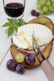 Französischer Ziegenkäse, Trauben und Glas Rotwein Stockfotos