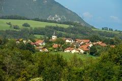 Französisches Dorf mit schönen Häusern, hoher Kirche und grünem landwirtschaftlichem Feld lizenzfreies stockfoto