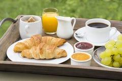 Französisches Frühstück mit Hörnchen, Kaffee und Orangensaft Stockfotografie