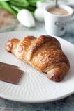 Französisches Hörnchen mit Schokolade und Kaffeetasse Lizenzfreies Stockfoto