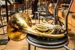 Französisches Horn, das auf dem Stuhl liegt Stockbild
