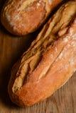 Französisches krustiges Brot, lokalisiert auf einem hölzernen Plankenhintergrund lizenzfreie stockfotografie