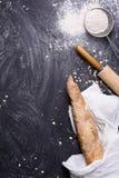 Französisches Stangenbrot oder rustikales Brot eingewickelt im weißen Tuch mit Nudelholz und Mehl über schwarzem Hintergrund Drau Stockfoto