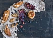 Französisches Stangenbrot schnitt in Karamellsoße der Stücke, der roten Trauben, der Blaubeere und des Salzes auf rustikalem dunk Lizenzfreie Stockbilder