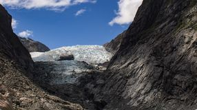 Edge of the ice at the Franz Josef Glacier in New Zealand. Franz Josef Glacier in the South Island of New Zealand with edge of ice shown among the rocks Stock Images