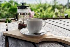 Franzosen bedrängen das Kaffeemaschine- und Kaffeetassestudio, das auf Tabelle mit Naturhintergrund beleuchtet wird Stockbilder