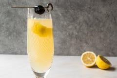 Franzosen 75 Champagne Cocktail mit Zitronen-Schale und schwarzer Olive Stockfotografie