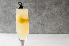 Franzosen 75 Champagne Cocktail mit Zitronen-Schale und schwarzer Olive Stockfoto