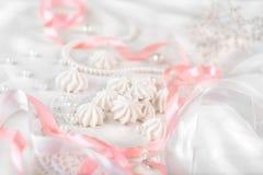 Französische Meringeplätzchen für Heiratshintergrund mit Perlen, rosa und weiße Satinbänder und -spitze Stockbilder