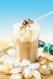 Frappe -在海滩背景的被冰的咖啡 免版税图库摄影