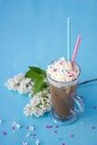 Frappe adornó con crema azotada y una rama de las lilas blancas fotos de archivo