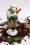 Frappe coffee. Ice milk coffee shake with mint and chocolate sticks, coffee beans on background Stock Image