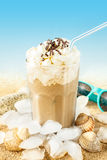 Frappe - iced coffee on beach background. Summer iced coffee (frappuccino, frappe or latte) with whipped cream in a tall glass on sand background - beach bar royalty free stock photography