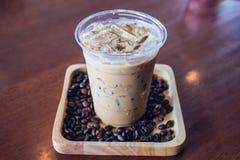 Frappe o frappuccino frío de la bebida del café en bandeja de madera con el grano de café imagen de archivo