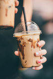 Frappe in plastic cup. Woman's hand holding a frappe in a plastic take-out cup Stock Images