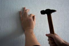 Frappement d'un clou dans le mur avec un marteau image libre de droits
