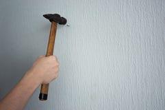 Frappement d'un clou dans le mur avec un marteau images stock